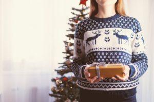 Frau im Norwegerpulli überreicht Weihnachtsgeschenk